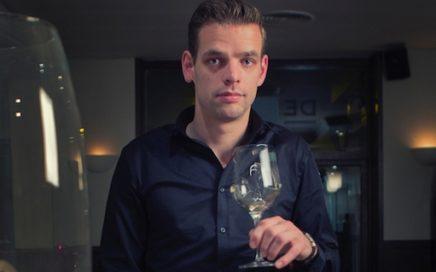 Foto van Kay met een wijnglas in zijn hand in het restaurant.