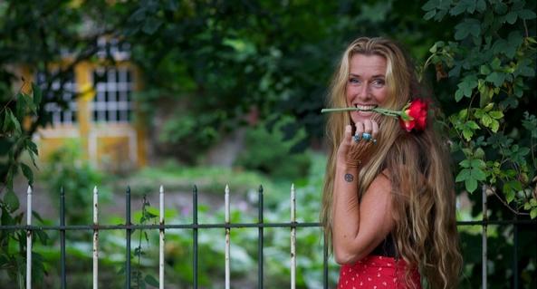 Foto van Anja Nijenhuis - van Wijngaarden met een rode roos tussen haar tanden.