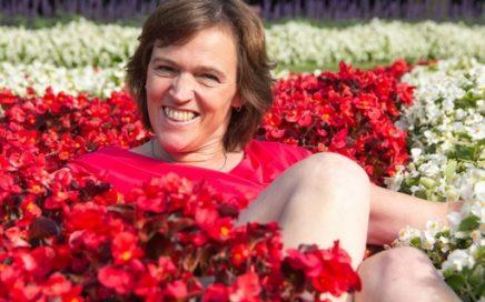 Foto van Corinne Hamoen tussen rode bloemen.
