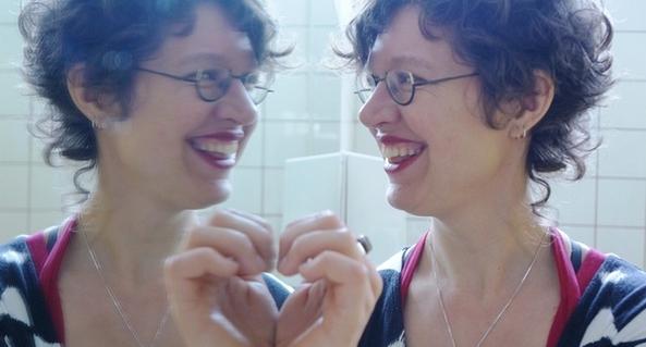 Foto van Marleen Bekker die zichzelf aankijkt in de spiegel.