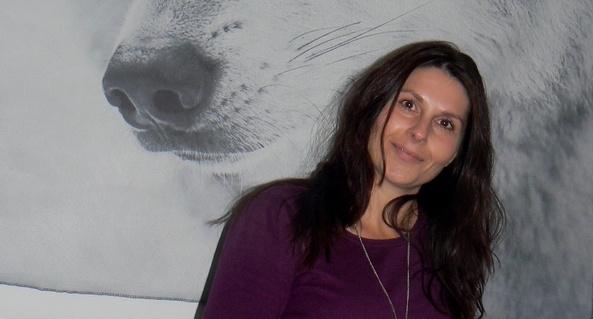 Foto van Sandra Meijers met op de achtergrond een grote foto van een hondensnuit.